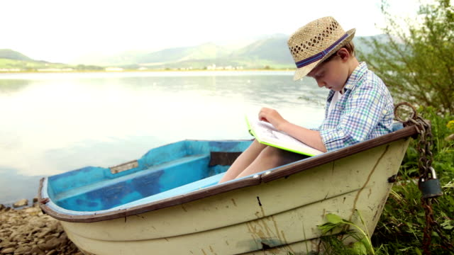 Little boy seats in the old boat and reads the book absorbedly video