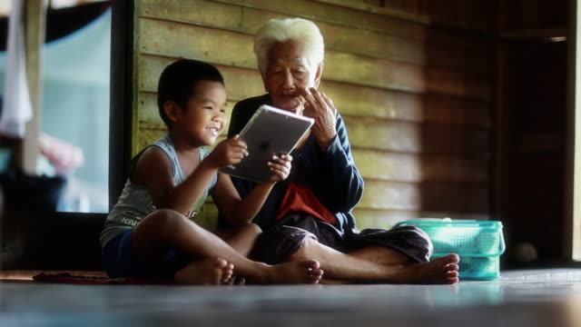 Little Boy Showing Something in Tablet to his Grandmother video