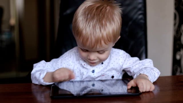 Little boy sitting at the table with the tablet. video