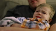 Little boy sitting on his dad's lap on the couch and being fussy video