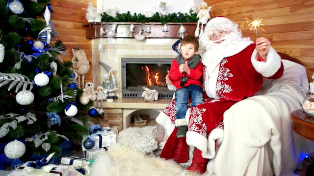 little boy sitting on Santa's lap with sparklers, holiday atmosphere, kid and happy santa claus video