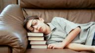 Little boy sleeps on the pile of books video