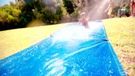 Little boy sliding down slippery water slide outdoors video