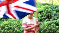 Little boy smiling and waving England flag outside video