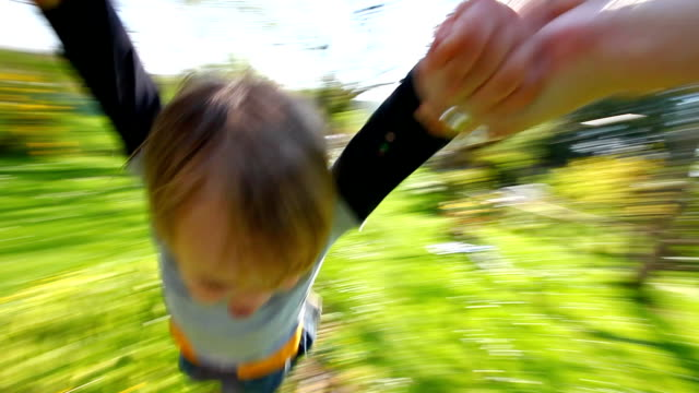 Little boy spinning around  in the family s garden video