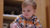 Little boy stacking plasticware on the kitchen floor video