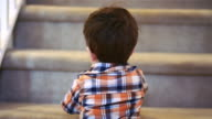 Little boy standing at the bottom of stairs, holding a sippy cup video
