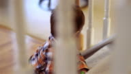 Little boy standing at the bottom of stairs, view through the railings video