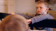 A little boy standing in the kitchen eating crackers with his sister video
