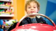Little boy swinging in a toy car video