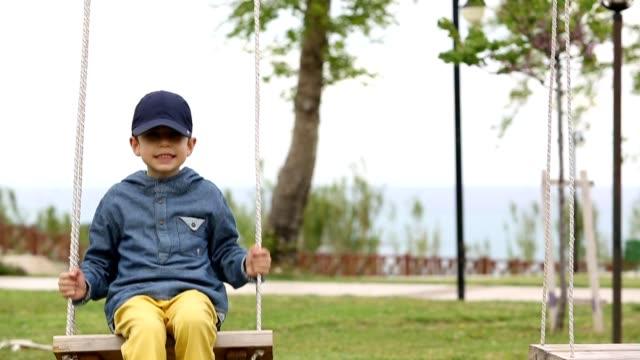 Little boy swinging  in park video
