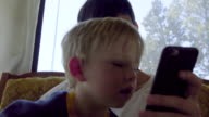 Little boy takes a closer look at a cell phone game video