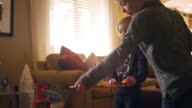 A little boy tells his little sister to stop playing with his toy car track in the living room video