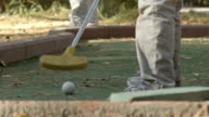 SLOW MOTION: Little boy tries to beat golf ball (back view) video