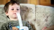 Little boy using nebulizer to inhale medicine video
