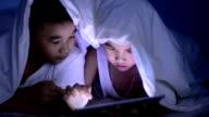 Little boy using tablet under the blanket video