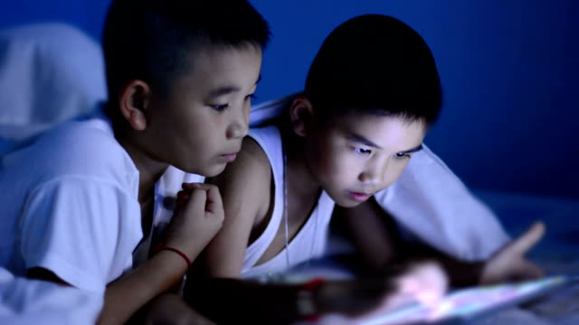 Little boy using tablet under the blanket video