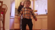 A little boy walking through the kitchen and living room to play with his toys video