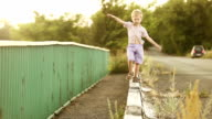 Little boy walks on the road curb video