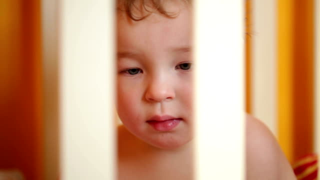 Little boy watching a film in the playpen. video