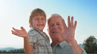SLO MO Little boy waving while being held by grandfather video