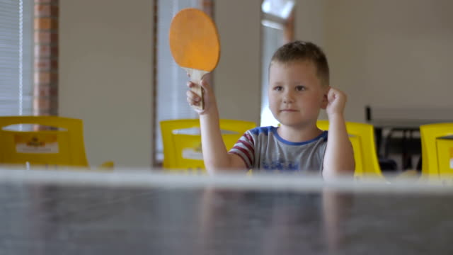 Little boy wearing american t-shirt playing ping pong video