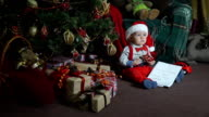 Little boy with a toy in the hands of sitting under the tree video