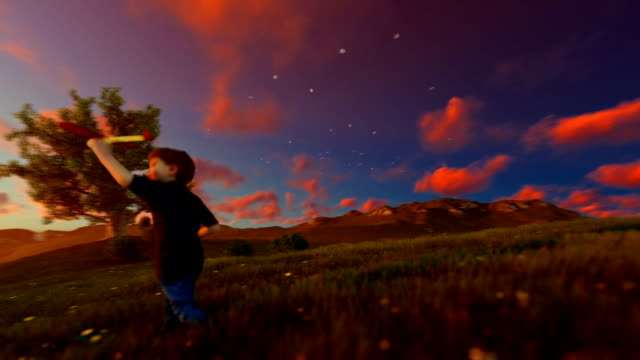 Little boy with airplane and grandfather resting on green meadow, sunrset, panning video