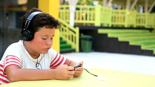Little boy with headphone using smartphone video