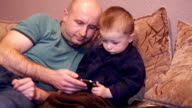 Little boy with his uncle watching a movie video