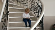 Little boy with tablet sitting on stairs of house. video