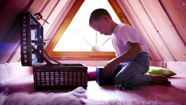 Little boy withdraws his treasures from the secret chest in the attic video