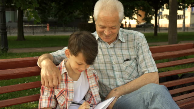 Little boy writes in his notebook what his grandpa says video
