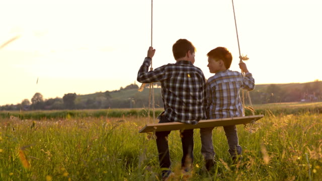 SLO MO Little boys swinging on the swing video