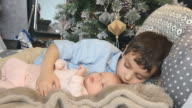 Little brother and newborn sister lie on a bed in Christmas video