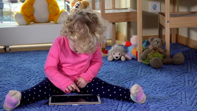 Little caucasian girl using tablet pc sitting on blue carpet video