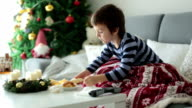 Little child, boy, blowing his nose and sneezing, lying sick in bed on Christmas video