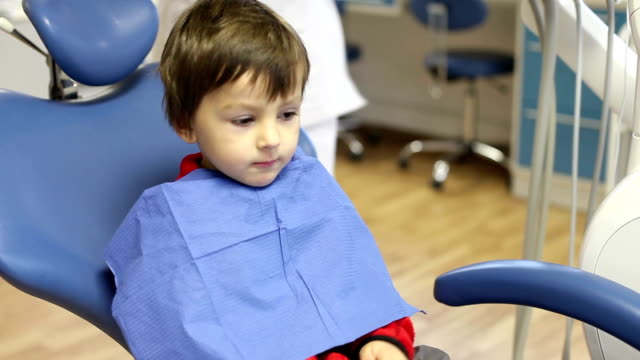 Little child, boy, sitting on a dentist chair, having his yearly checkup video