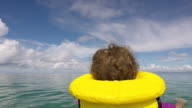 Little child floating with a life jacket alone in the ocean video