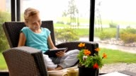 Little child girl sitting on the terrace in armchair with digital tablet video