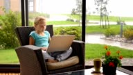 Little child girl sitting on the terrace in armchair with laptop video