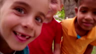 Little children being silly with friends and smiling into the camera video