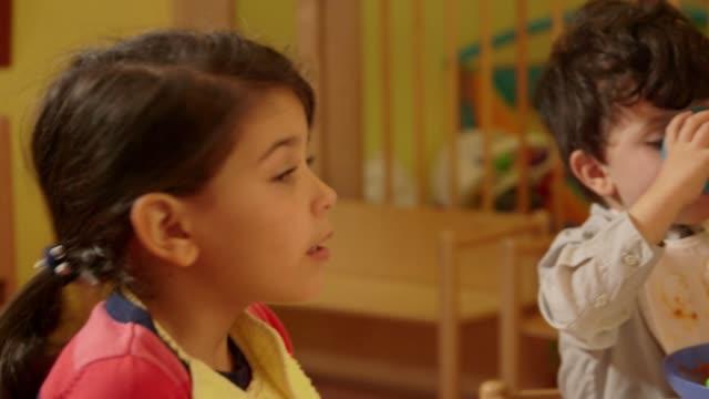 Little children, child, girl, boy, eating food in kindergarten, preschool video