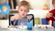 Little children painting in the classroom, camera move, HD video video