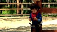Little Cowboy standing near a wooden fence video