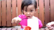 A little cute asian girl enjoy eating ice-cream with mother. slow motion video