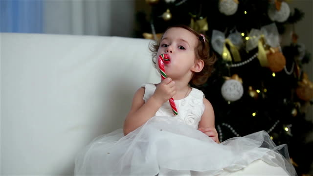 Little cute girl eating a piece of candy on the eve of Christmas video