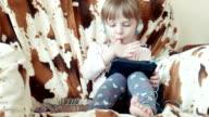 Little cute girl look cartoons on digital tab video