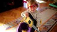 Little cute girl playing toy guitar and singing video