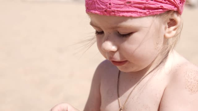 Little cute girl playing with sand and seashells on the beach. Close up in UHD video